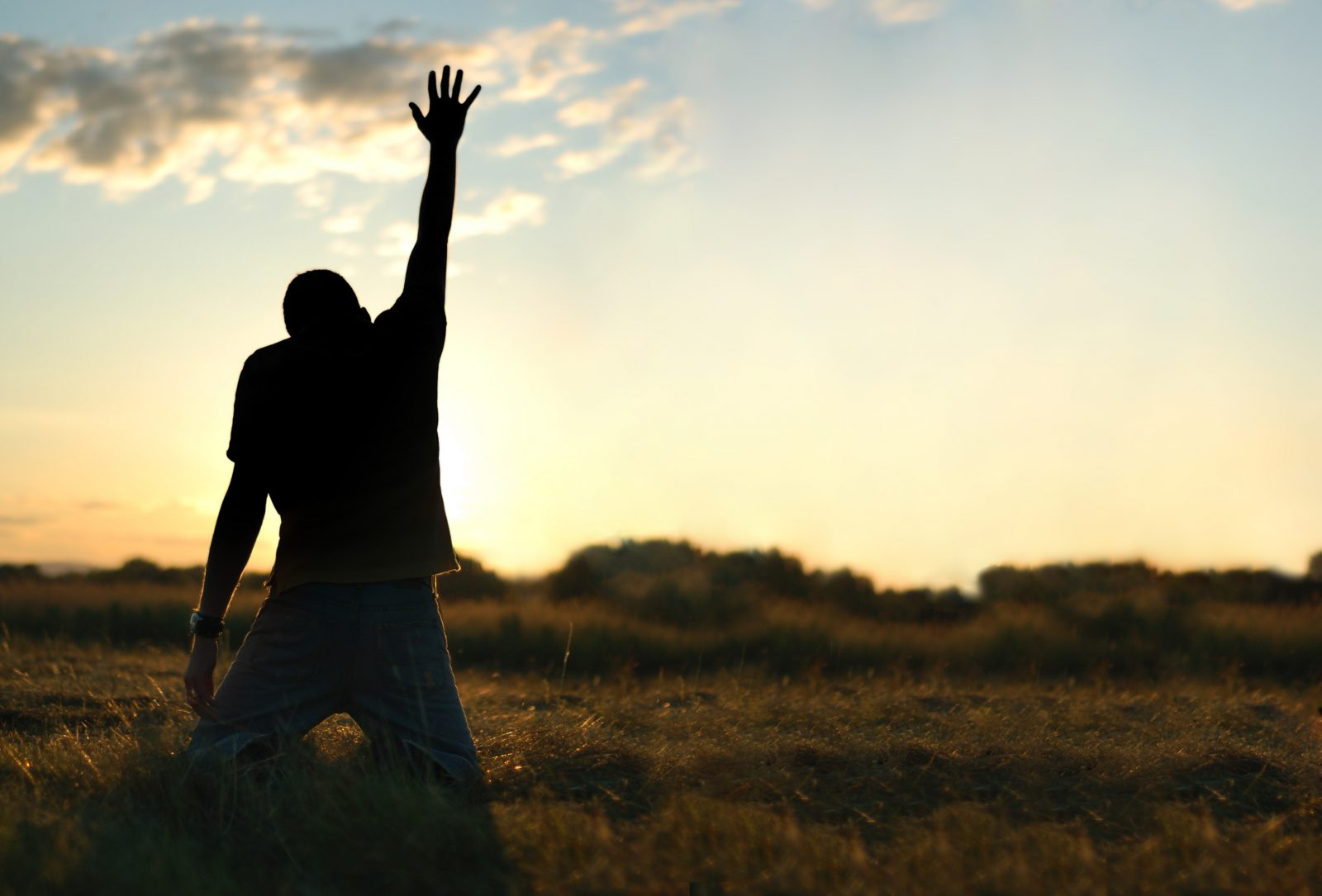Young man on his knees reaching up to heaven with an outstretched arm.